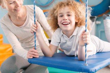 Happy child lying on swing