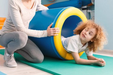Child exercising with play tunnel