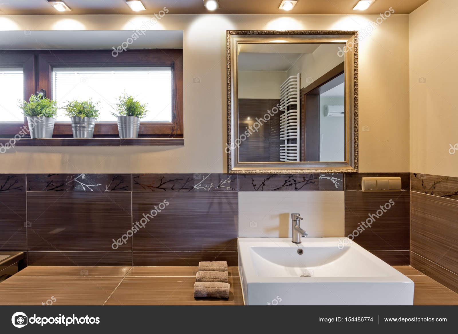 Van Boven Badkamers : Bruin badkamer met spiegel boven de wastafel u stockfoto