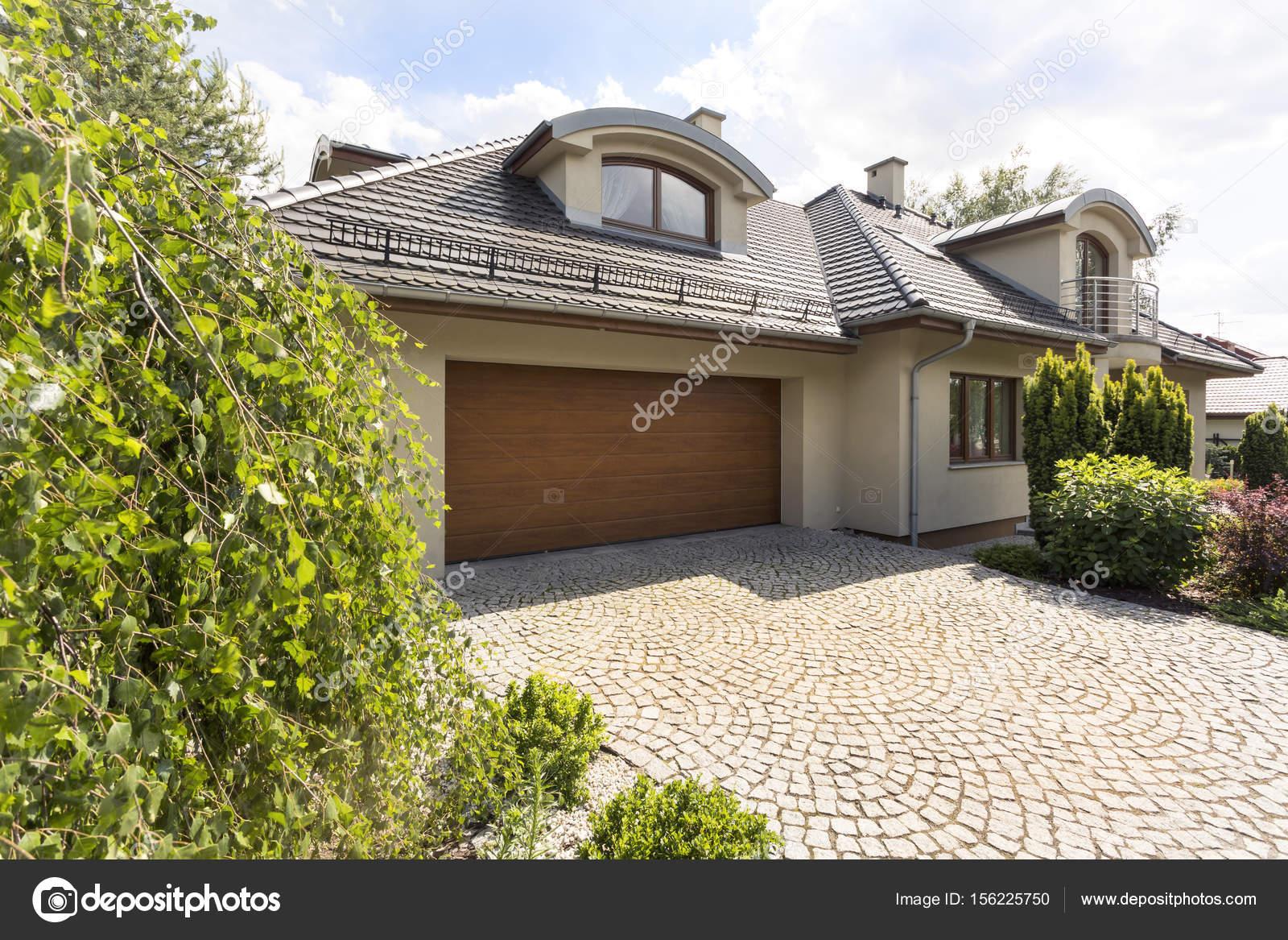 Exterior de la casa con entrada de autos de adoquines for Casa con garage laterale