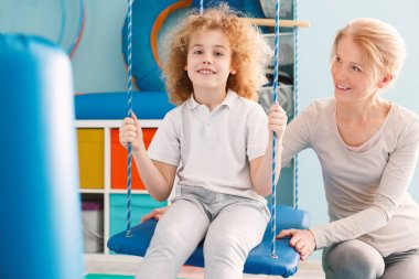Boy sitting on a swing during therapy