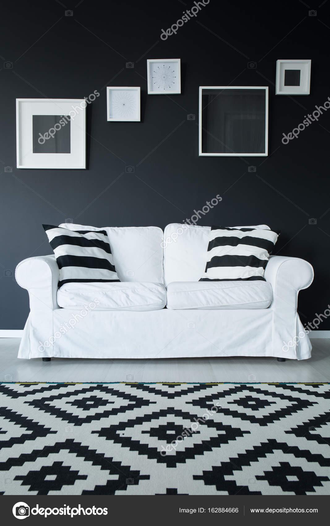 c220906d5cbb28 Gemusterten schwarzen und weißen Teppich auf Panel Boden vor weißen Sofa  mit gestreiften Kissen — Foto von ...