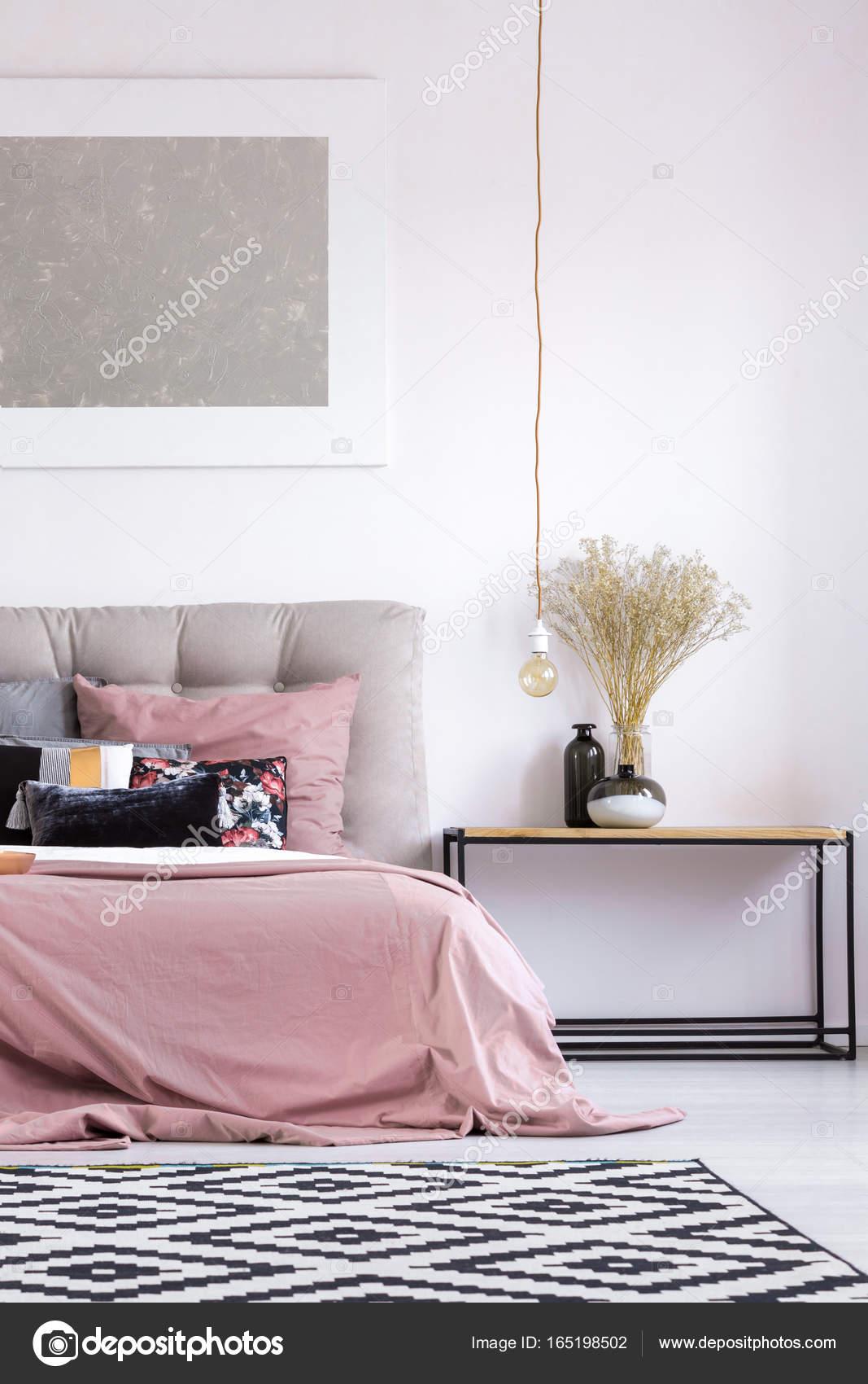 bloemen in vaas op houten tafel en koperen lamp in pastel gezellige slaapkamer met grijs schilderen op de muur foto van photographeeeu
