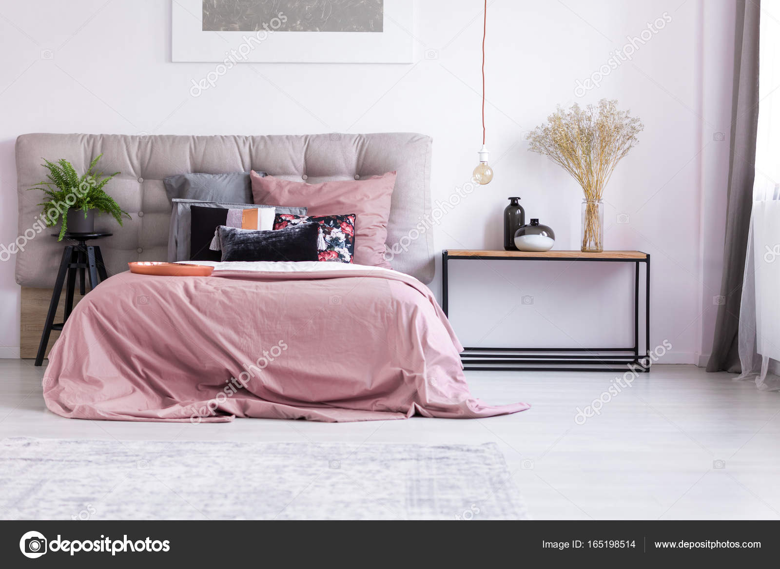 bloemen in glasvaas op tafel en koper gloeilamp in pastel roze slaapkamer met plant op kruk foto van photographeeeu