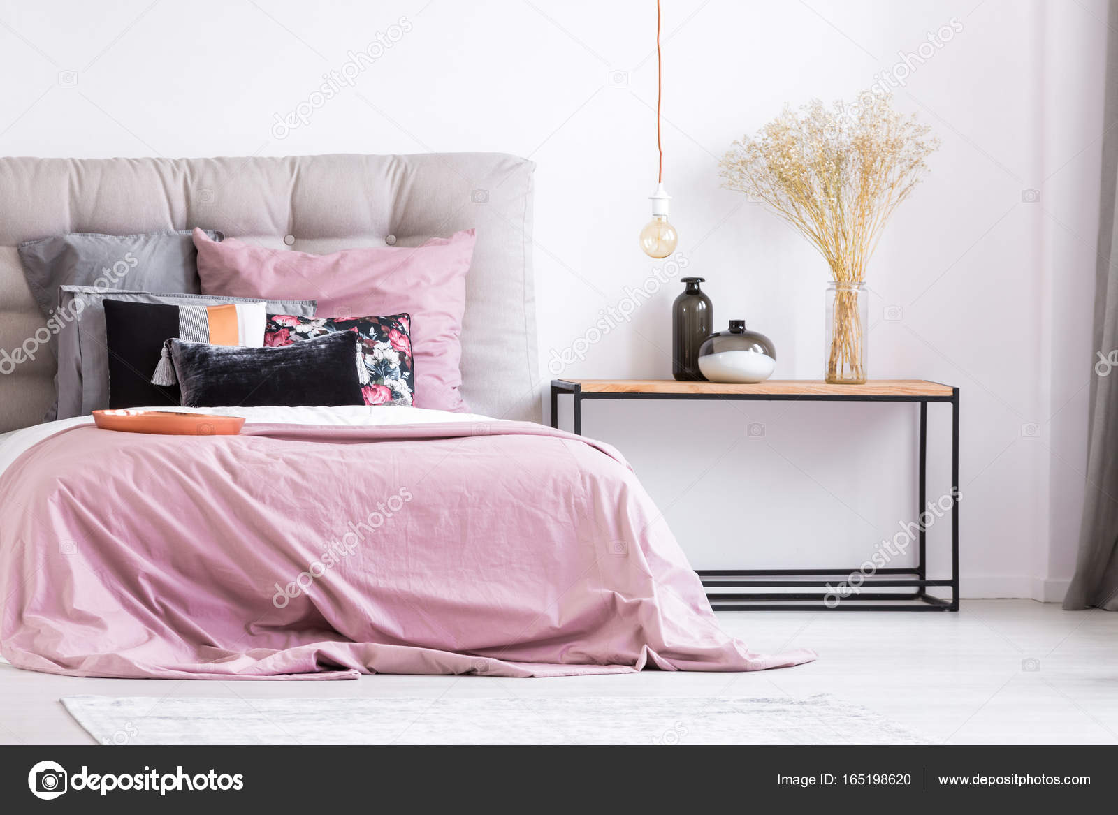 decoratieve vazen en bloemen op tafel in pastel roze slaapkamer met koperen plaat en patroon kussens op kingsize bed foto van photographeeeu