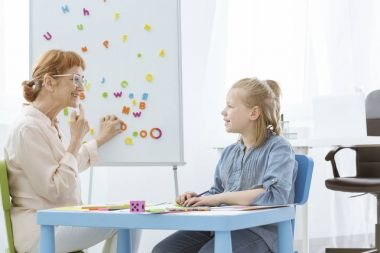 Speech therapist practicing with girl
