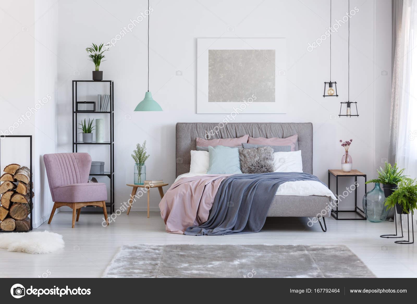comfortabele poeder roze stoel naast plank met brandhout in zachte pastel slaapkamer met decoratieve glazen vazen foto van photographeeeu