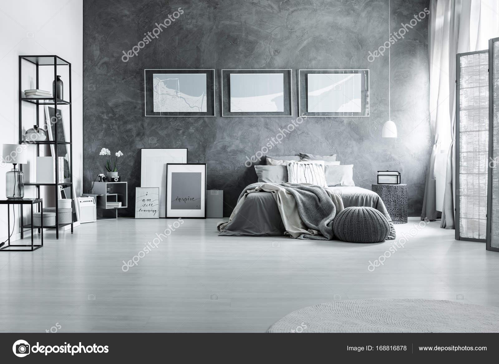 quilt op kingsize bed tegen de betonnen muur met wit posters in chique zwart wit slaapkamer grijs foto van photographeeeu