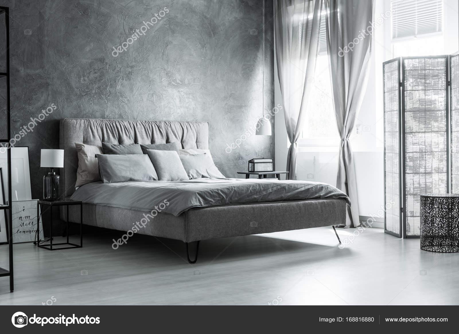 donker grijs slaapkamer met comfortabele kingsize bed onder venster met decoratieve gordijnen en scherm foto van photographeeeu