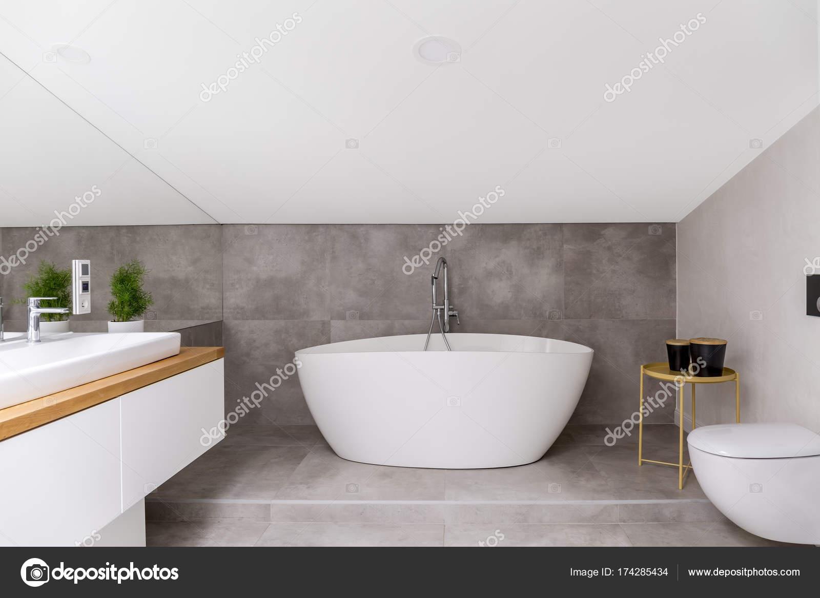 Vasca da bagno ovale contro smalto grigio u foto stock