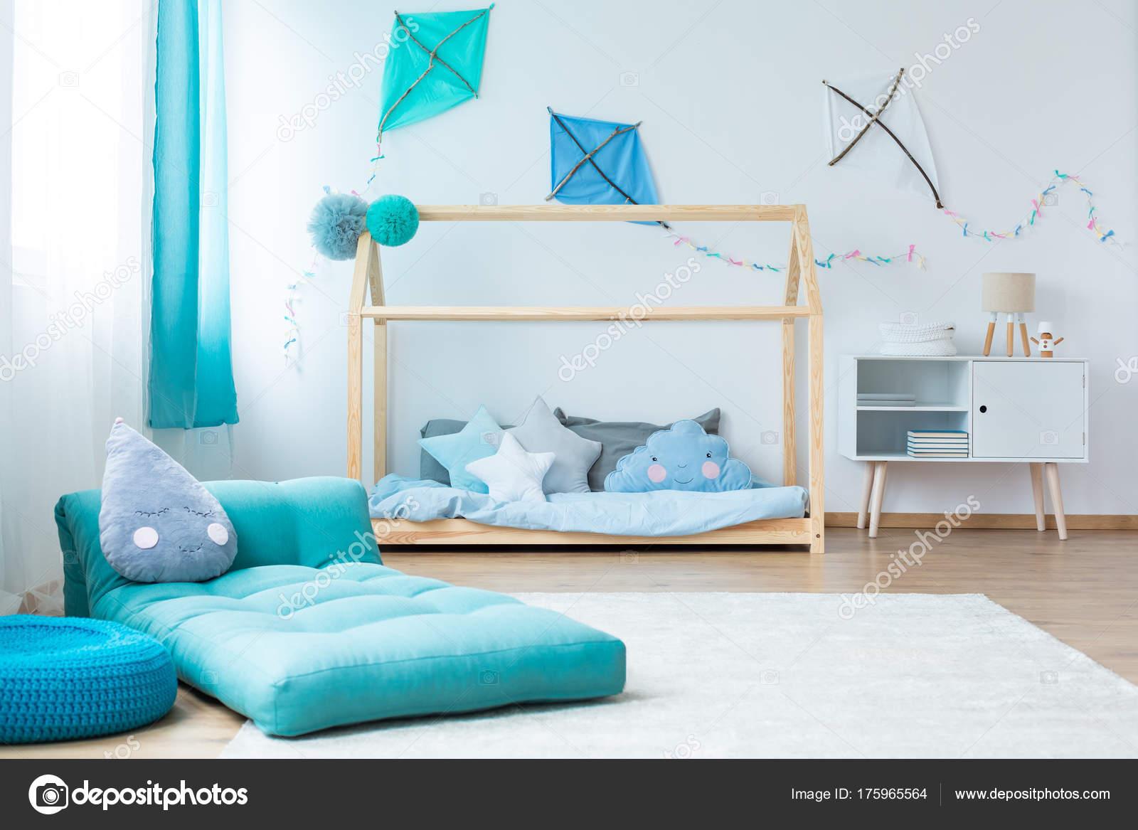 blauwe matras op witte tapijt in blauw kind slaapkamer met diy vliegers op de muur boven de kast en bed foto van photographeeeu