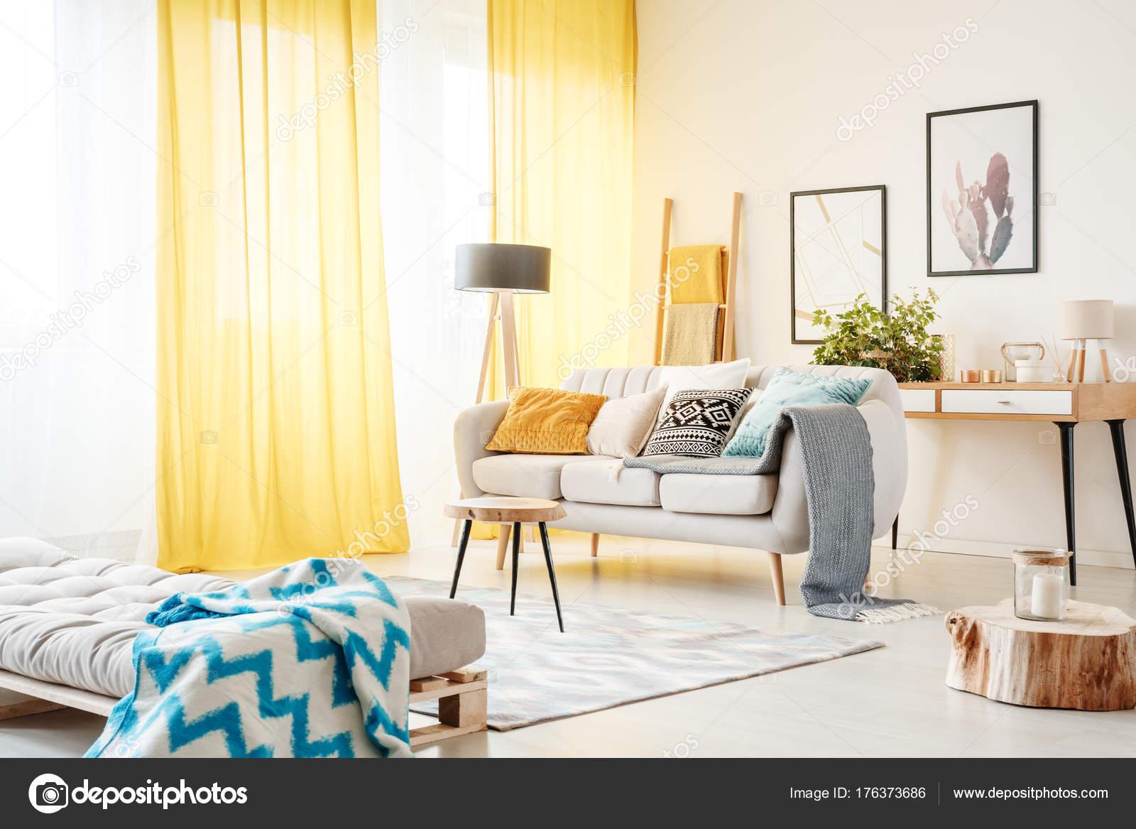 Gemusterte Decke Auf Sofa Und Kerze Auf Hölzernen Stumpf Im Geräumigen  Wohnzimmer Mit Gelben Vorhänge Und Beige Sofa U2014 Foto Von Photographee.eu