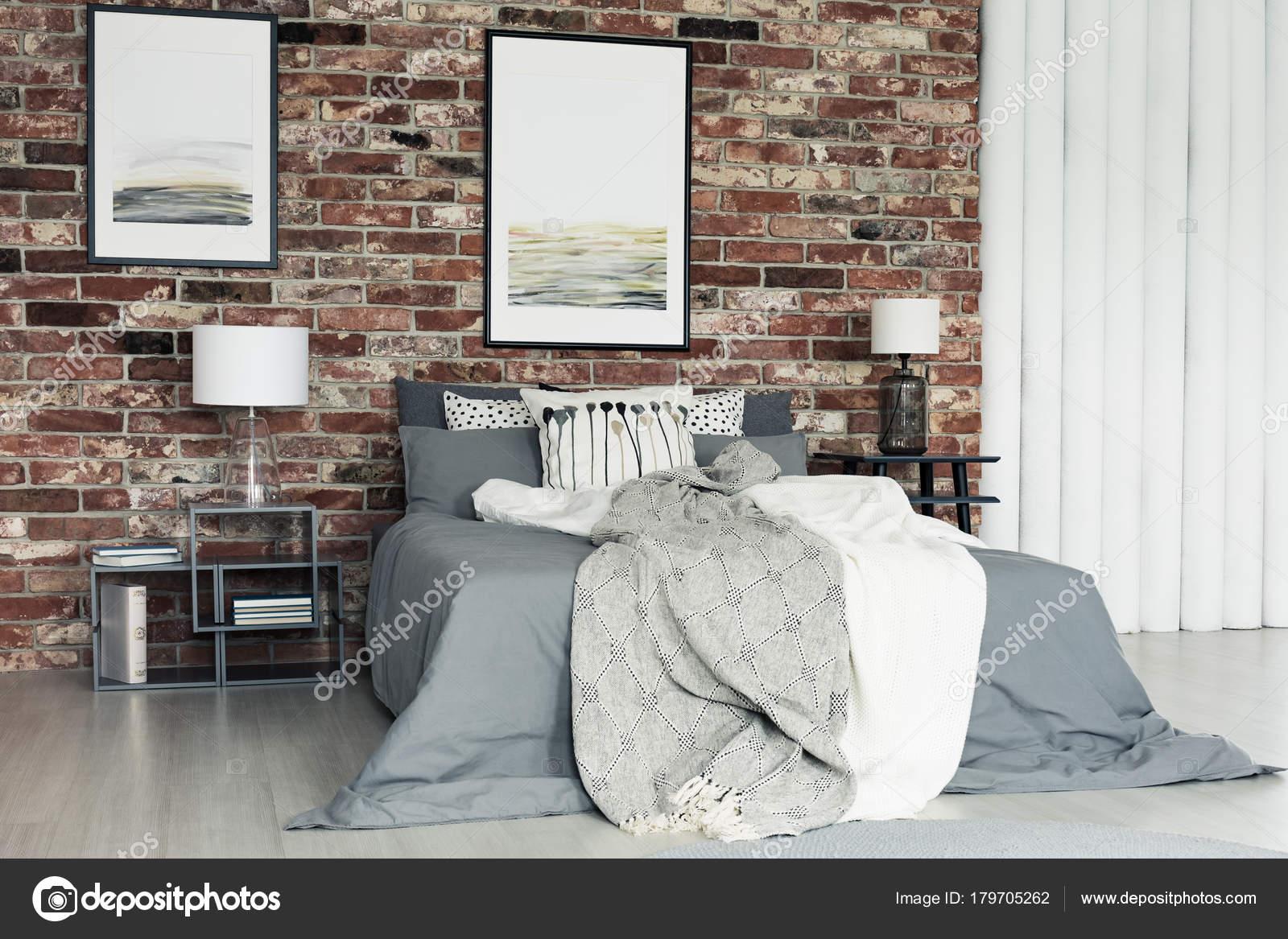 grijze bedlinnen op kingsize bed tussen nachtkastjes met lampen tegen een bakstenen muur met schilderijen in slaapkamer foto van photographeeeu