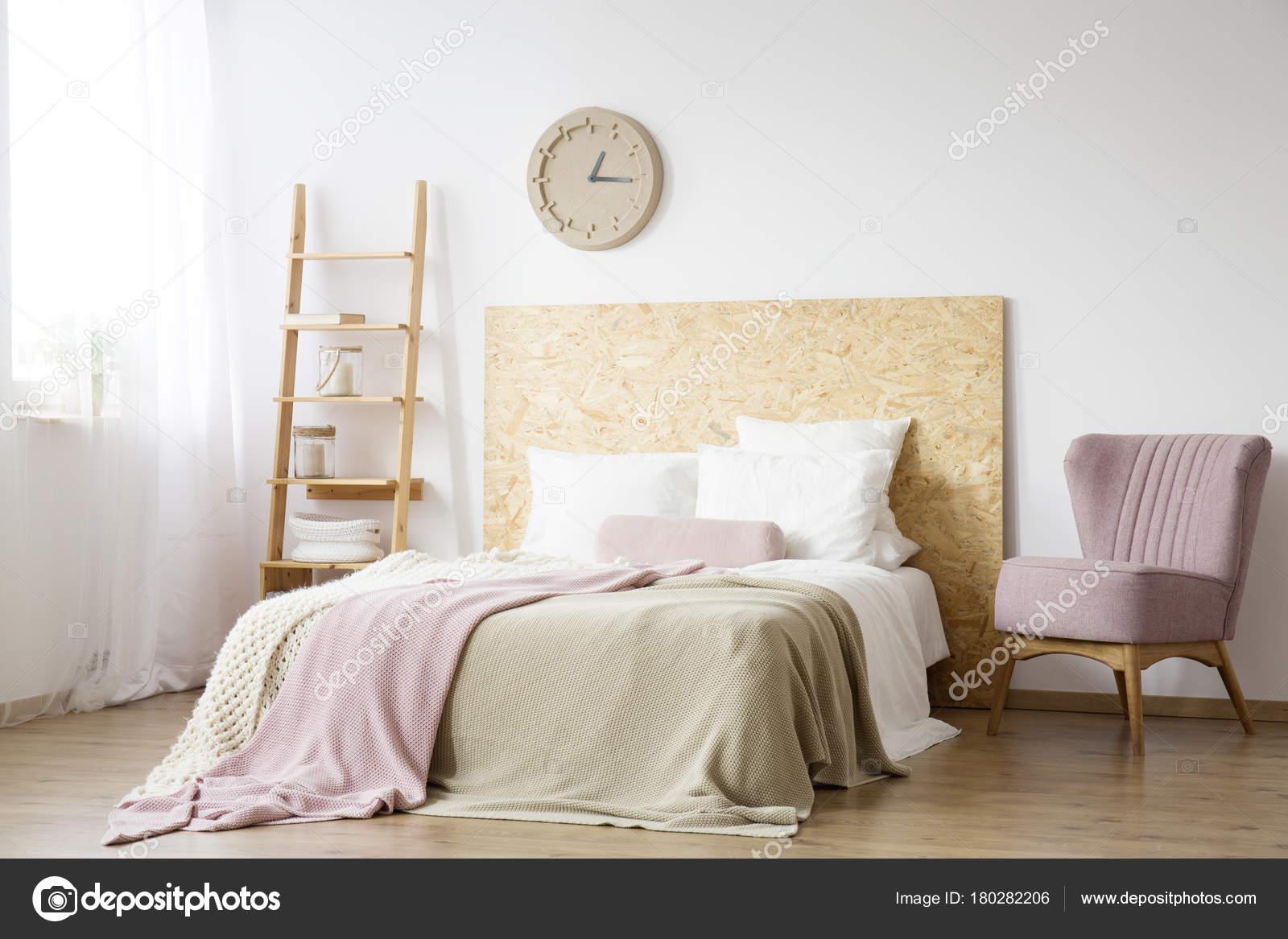 roze fauteuil in natuurlijke slaapkamer stockfoto