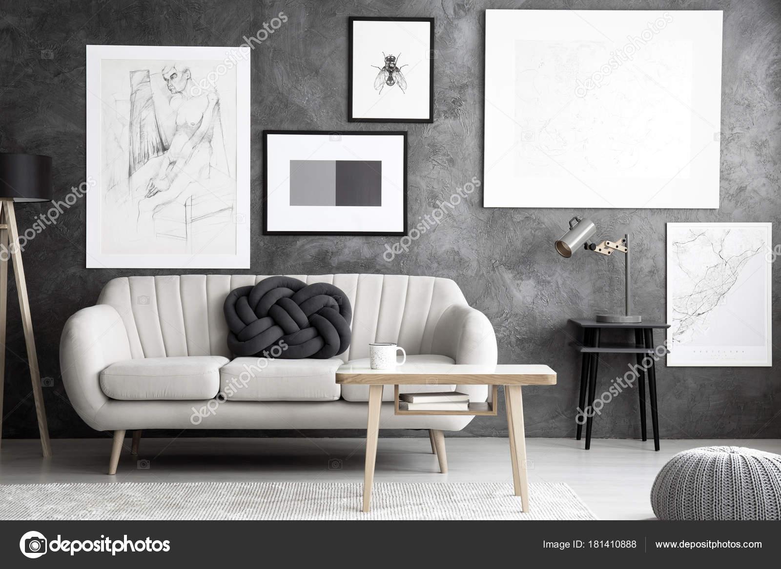 lamp op kruk naast beige sofa met knoop kussen in grijs woonkamer interieur met houten tafel foto van photographeeeu