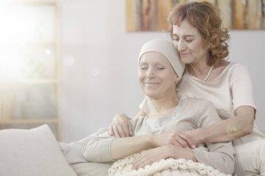 Mother hugging happy sick woman