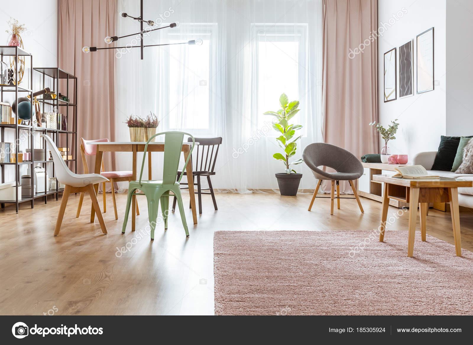 houten tafel roze deken en mint en grijze stoel in ruime interieur met gordijnen en plant foto van photographeeeu