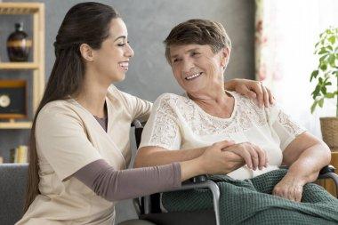Nurse supporting happy elderly woman