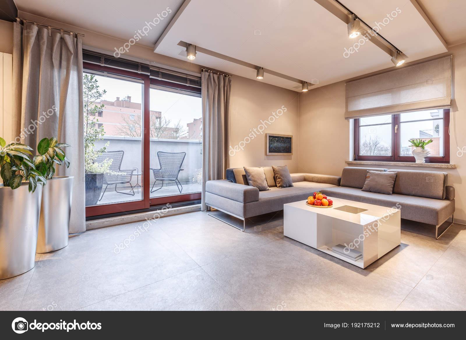 bruin ruime en moderne woonkamer interieur met een grijze bank tafel bloempotten gordijnen en balkon schuifdeuren foto van photographeeeu