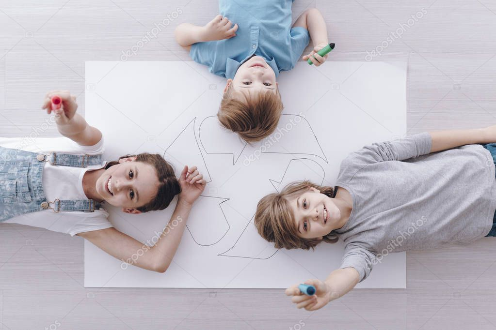 High angle of group of smiling kids lying on the poster with recycling sign