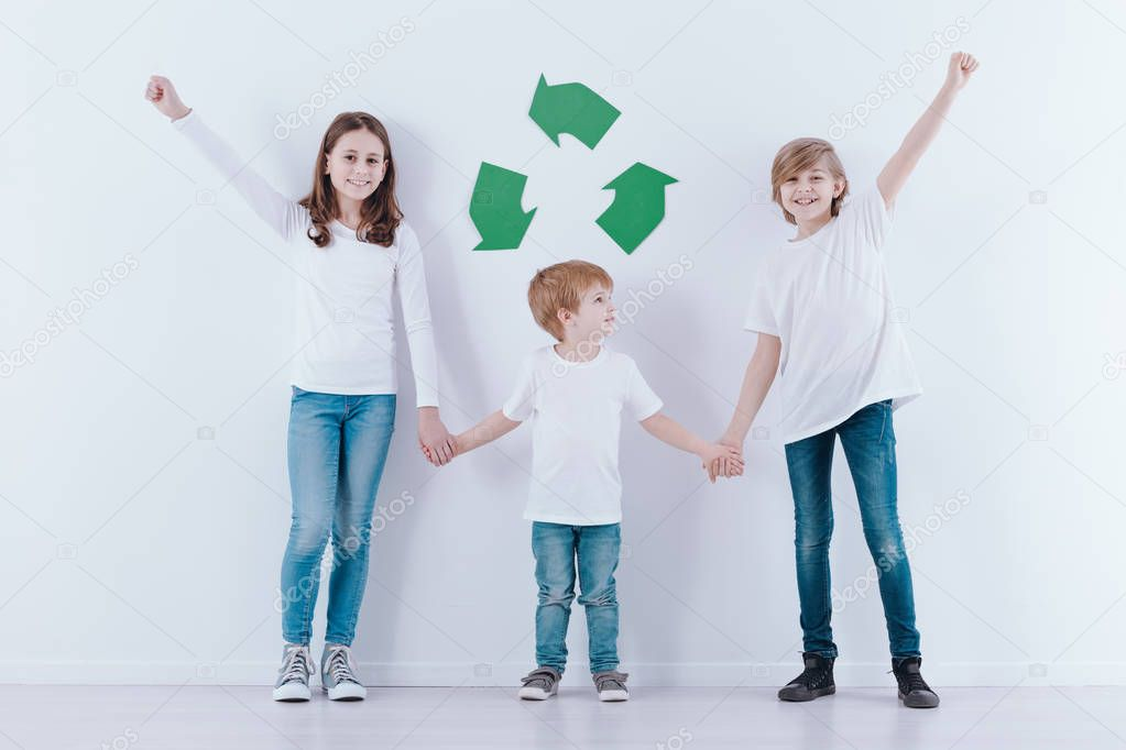 Children holding hands against white background with green symbol of recycling