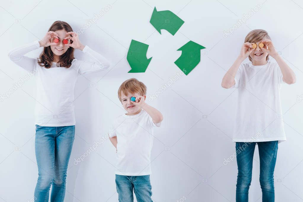 Happy children with colorful corks against white wall with green recycling symbol