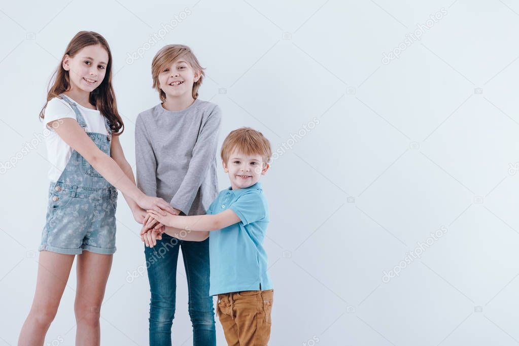 Children holding hands as a gesture of support, isolated on white background