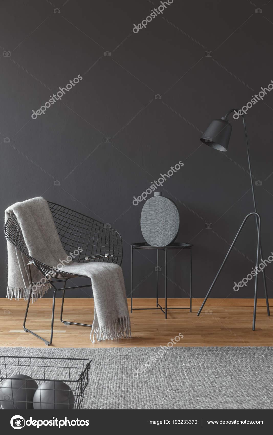 ontspannen leeshoek woonkamer interieur met grijze deken metalen fauteuil tegen stockfoto