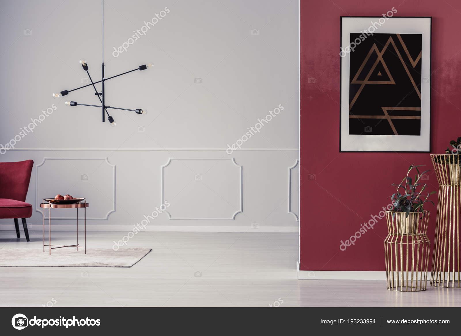 Planten goud potten tegen rode muur met zwarte poster woonkamer