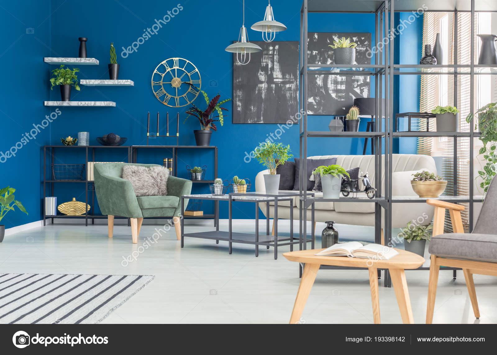 groene fauteuil tegen marine blauwe muur woonkamer interieur met zwarte stockfoto