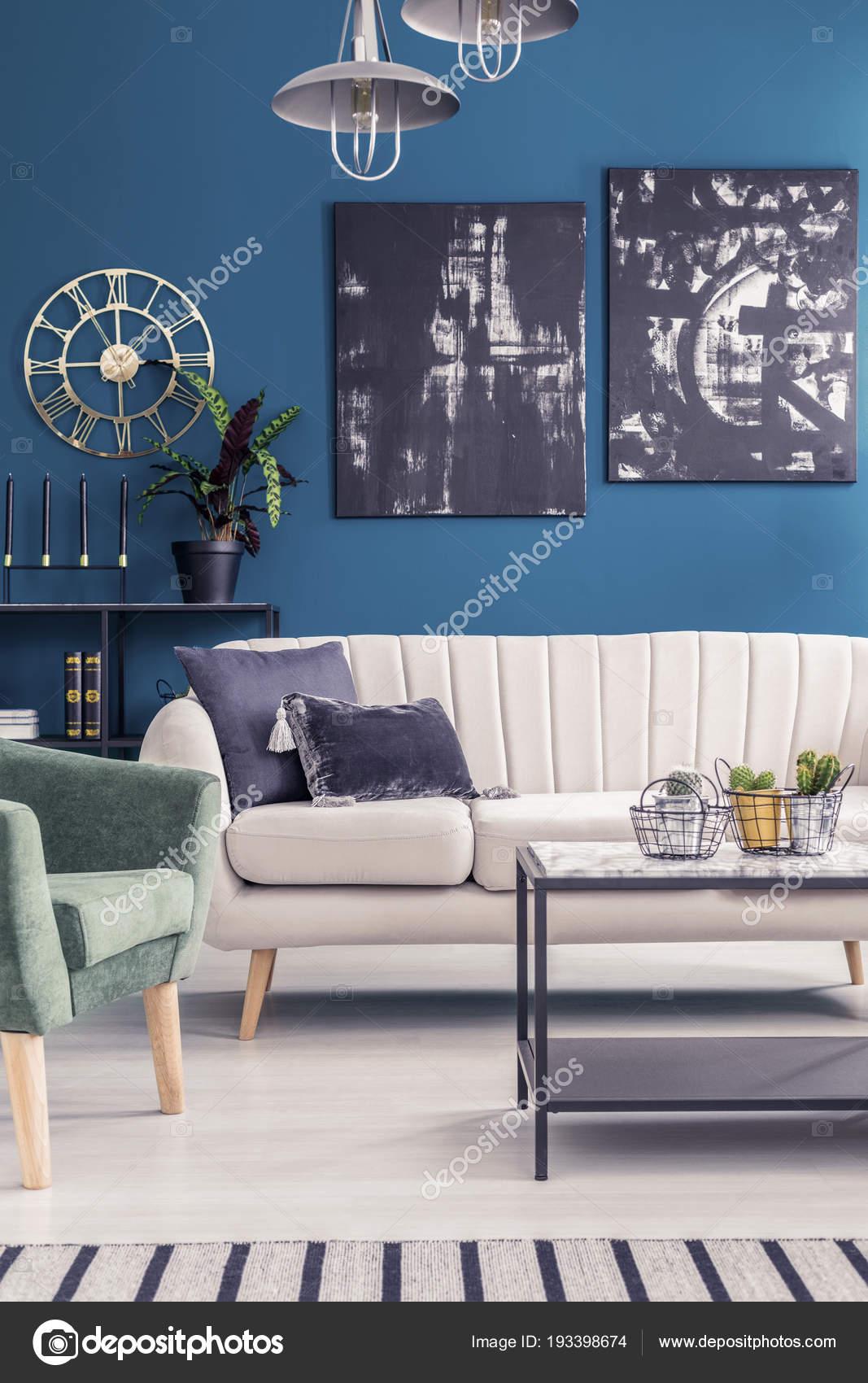 gouden ronde klok zwarte schilderijen blauwe muur woonkamer interieur met stockfoto