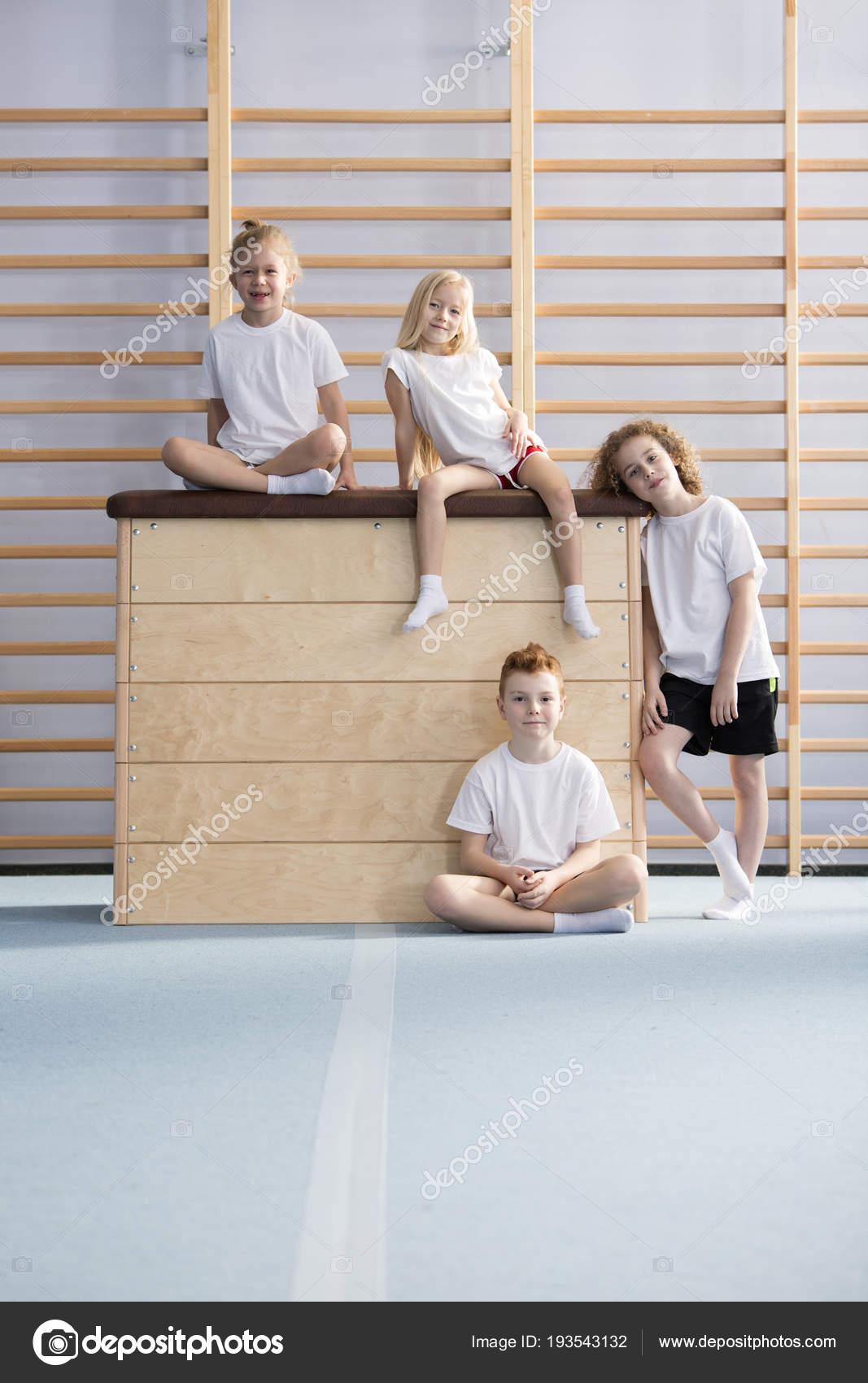 Grupo de niños felices en trajes de deporte sentado en una caja de madera  de la bóveda - el chico sobre la caja de madera descargar — Foto de  photographee. ...