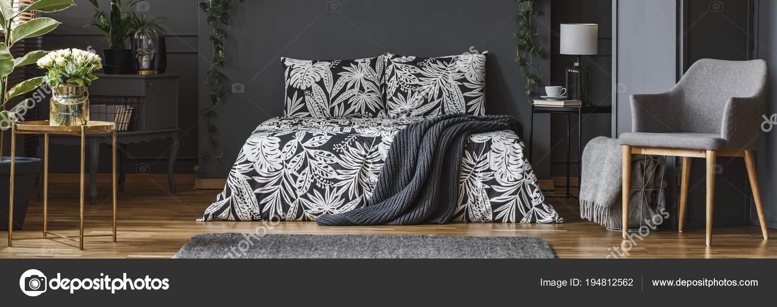 donkere slaapkamer met florale bed stockfoto