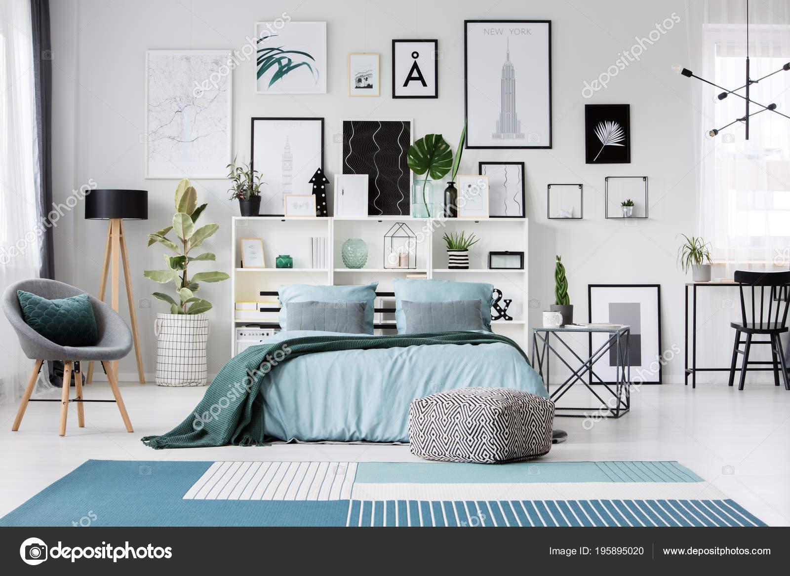 Blauw tapijt poef bij bed ruime slaapkamer interieur met grijze