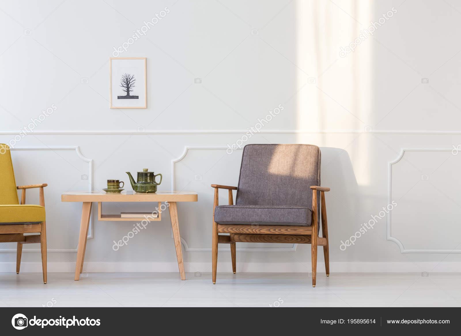 Grijs houten fauteuil naast tabel minimale woonkamer interieur met