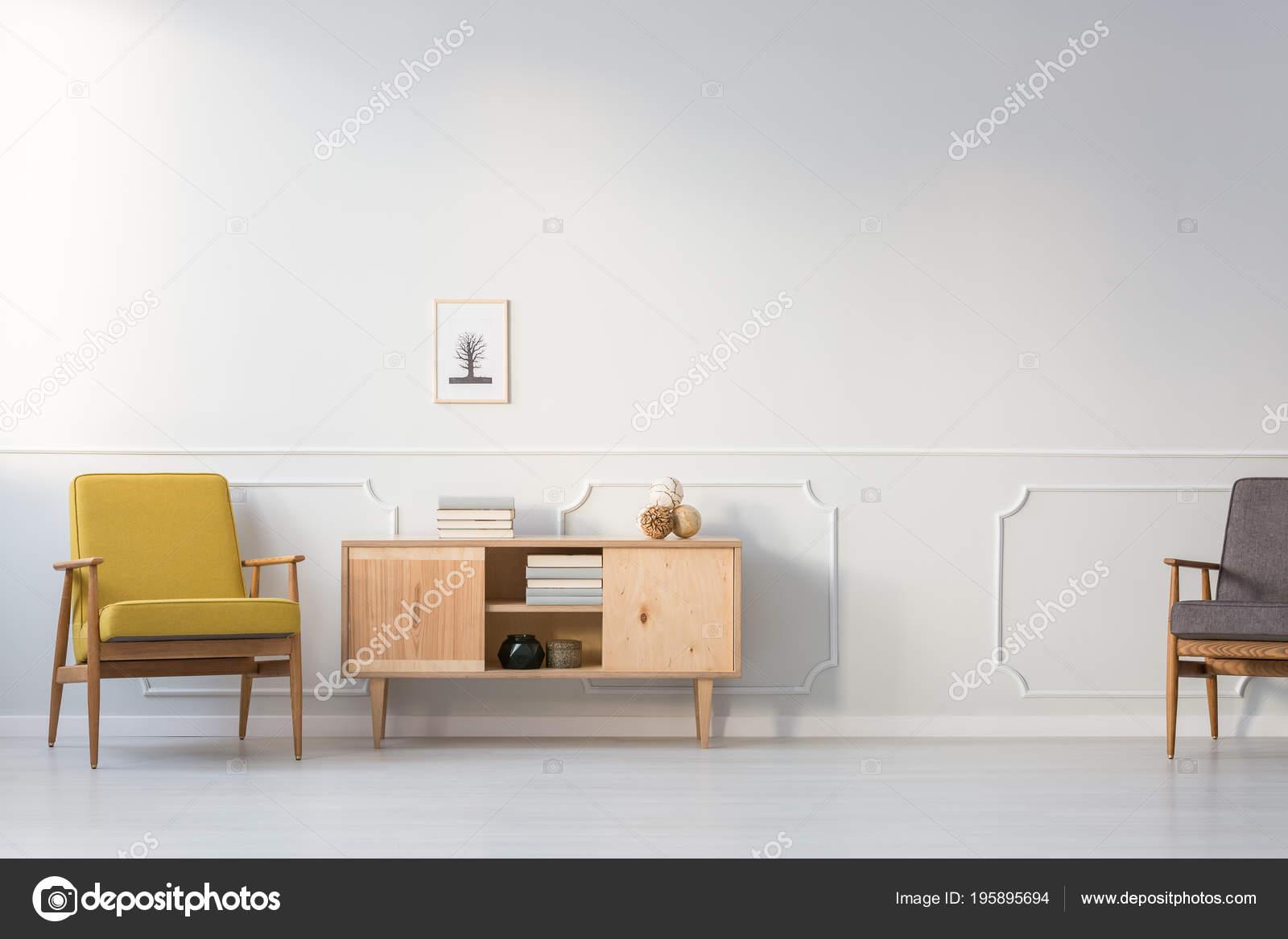 Gele Vintage Fauteuil Naast Houten Kast Tegen Een Witte Muur