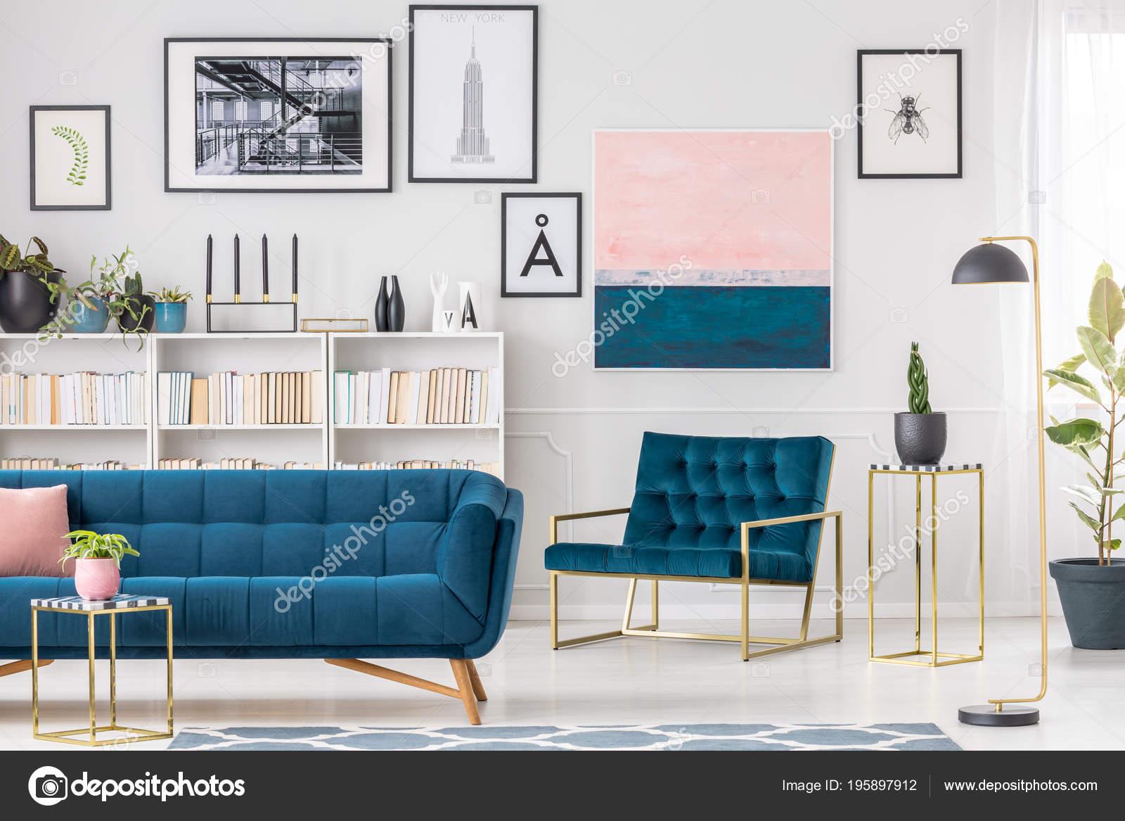 artistieke woonkamer interieur met blauwe bank en fauteuil schilderijen en gouden tabellen foto van photographeeeu