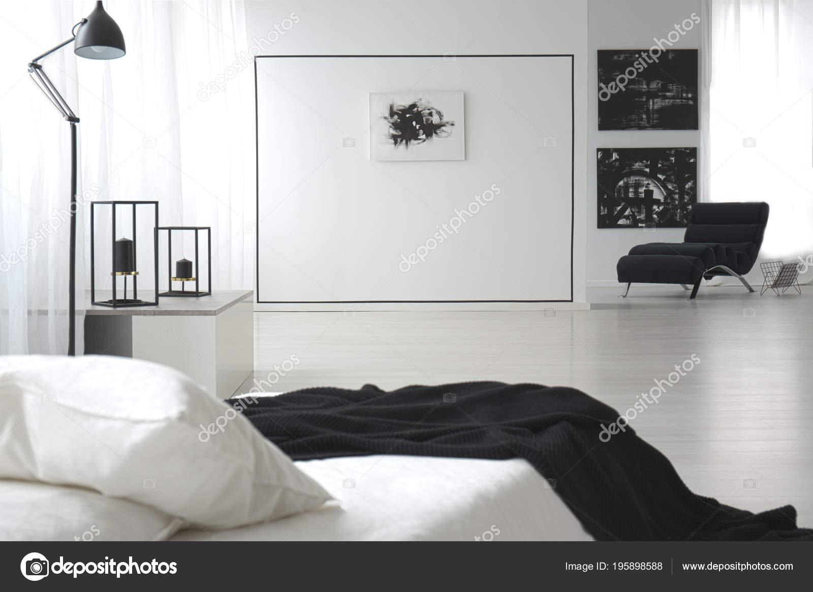 zwart wit slaapkamer interieur met schilderijen dubbel bed lamp muur stockfoto
