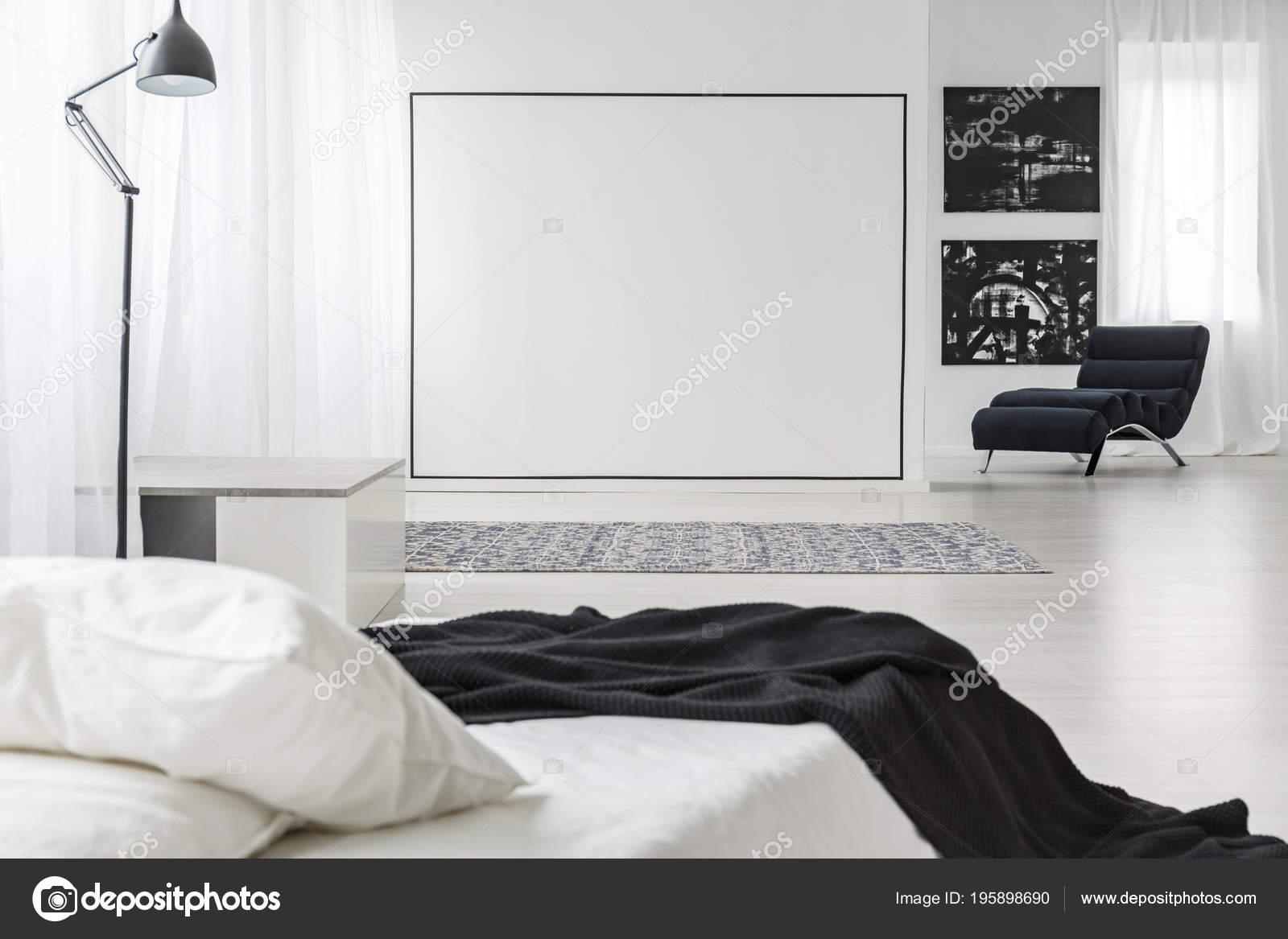 Black square decoration on a white wall in minimalistic bedroom interior with lamp paintings and bed photo by photographee eu