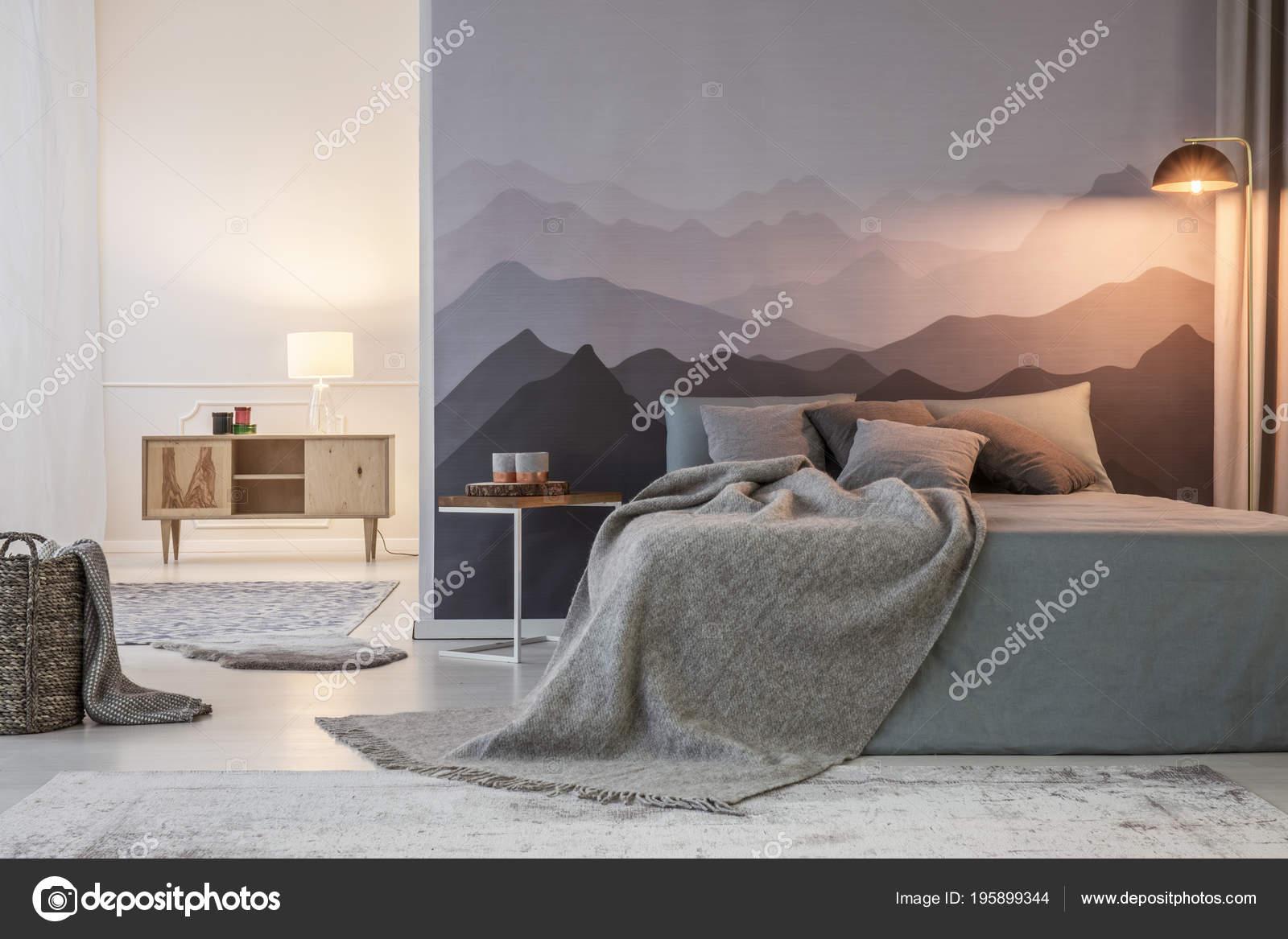 Grigia coperta letto contro sfondo montagna accanto uno sgabello con