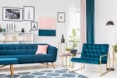 Boční úhel modré obývacího pokoje interiéru s růžové a zlaté akcenty