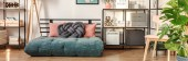 Photo Green futon mattress with dirty pink pillows and dark grey knot cushion in bright teenage girl room interior