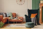 Ohrensessel mit Kissen im modernen Wohnzimmer mit grauer und grüner Wand