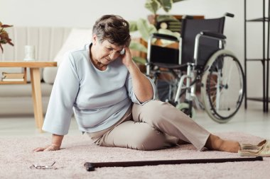Elder woman sitting on a floor next to a cane and having a headache