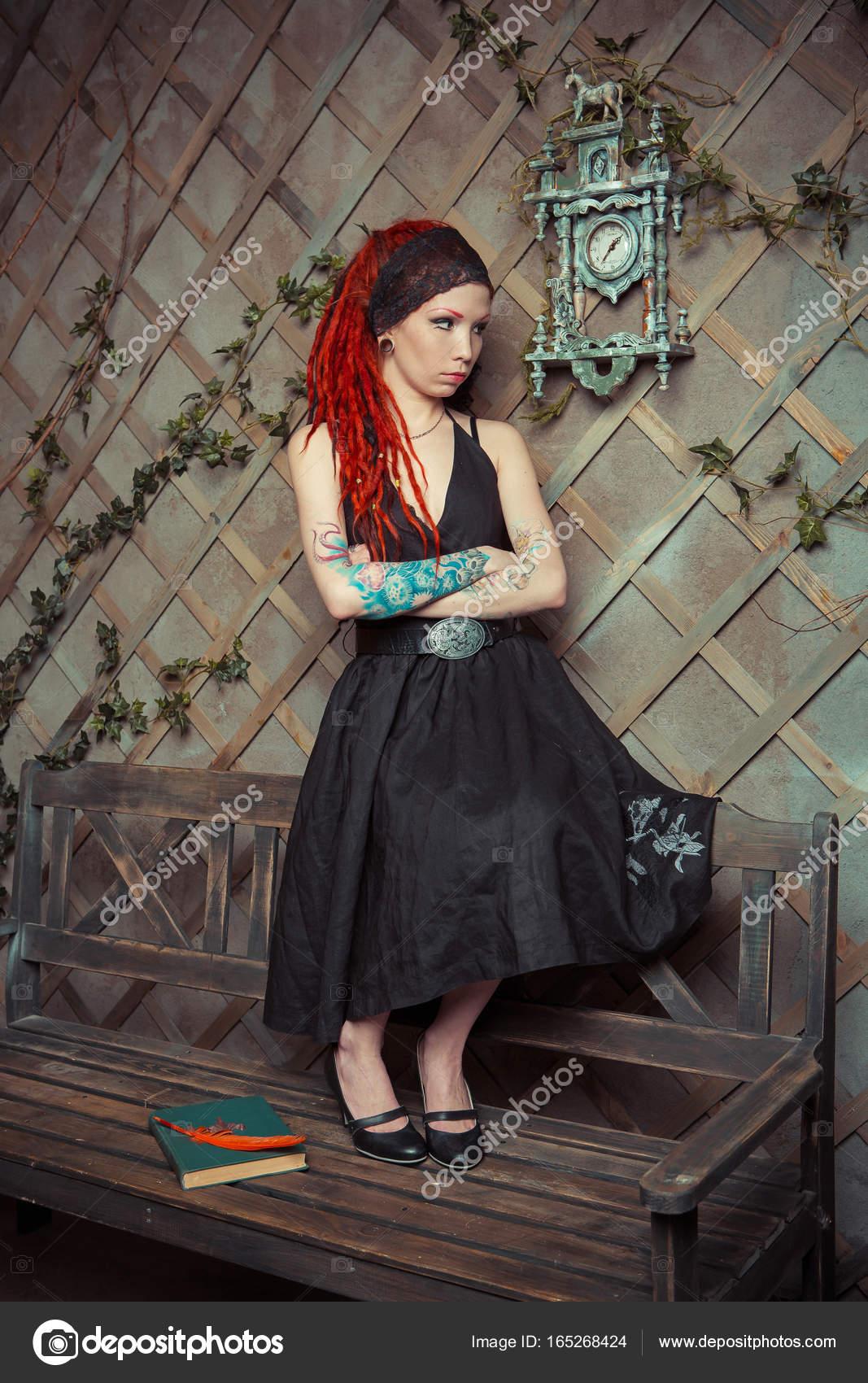 dbbdb368febdfc Getatoeëerd meisje met rode dreadlocks