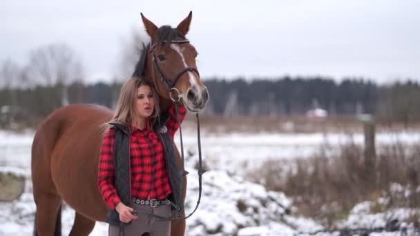 Krásná dívka v módní košili procházky s koštětem koně na začátku zimy.
