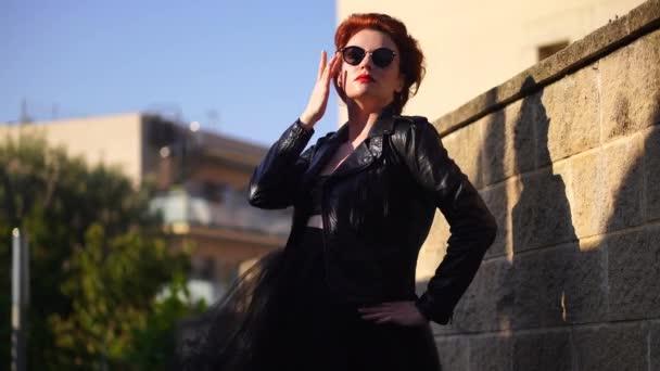 Krásná zrzavá žena v černé kožené bundě a brýlích