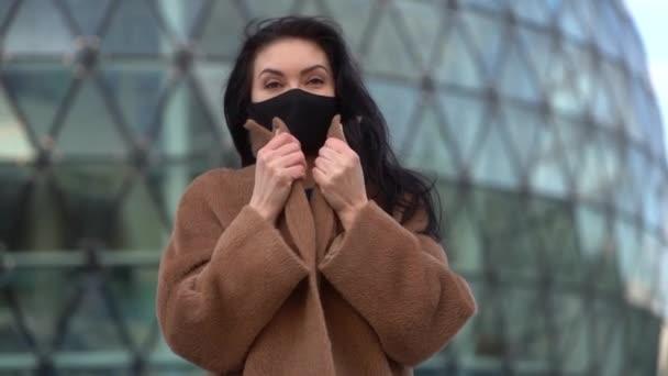 egy fekete maszkos és bézs kabátos nő portréja