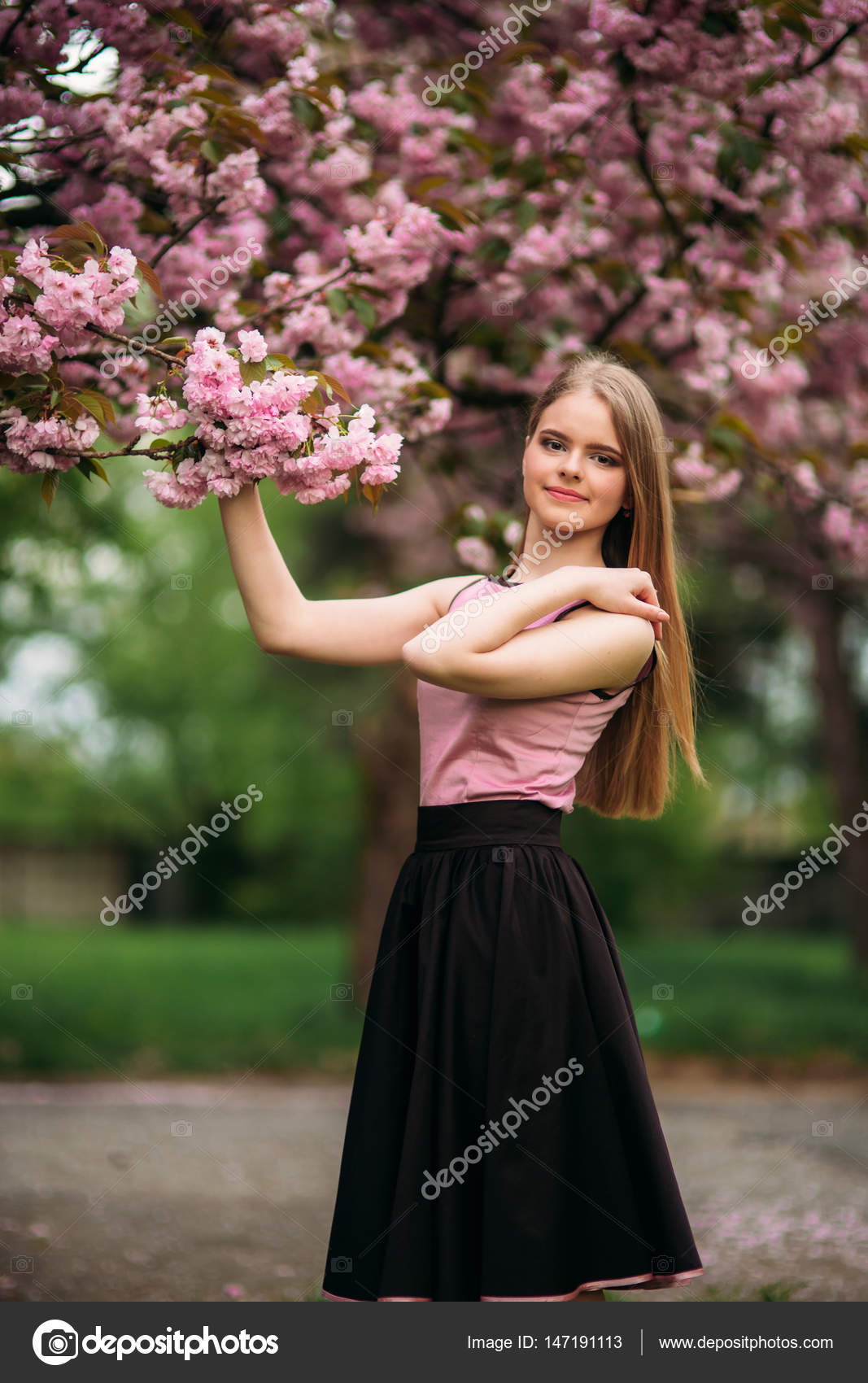 a02caa964 Encantadora chica de blusa rosa y falda negra posa para los ...