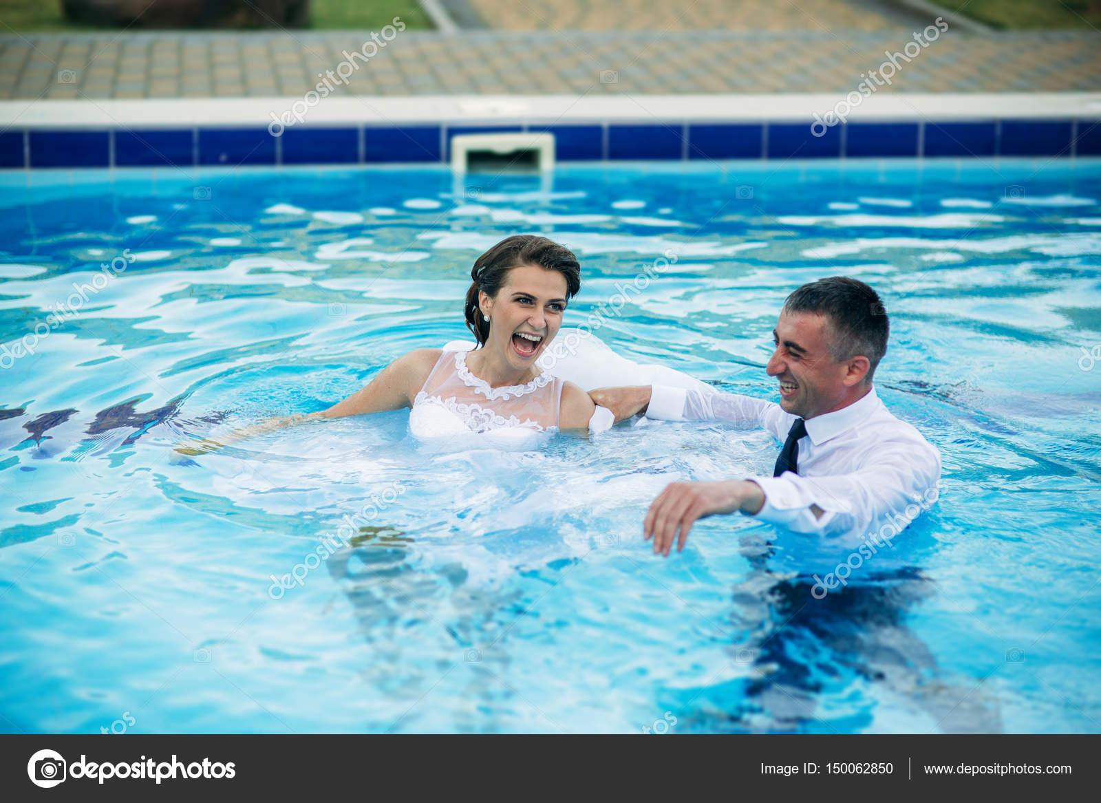 Pareja joven esposos saltando en la piscina con un traje for En la piscina